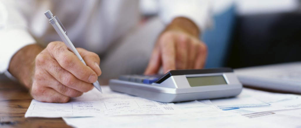 mid section view of a businessman using a calculator in an office